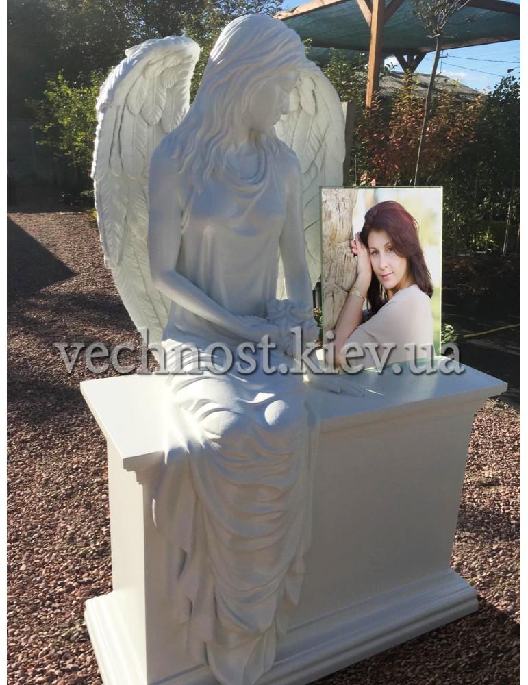 Памятник ангел, сидящий на тумбе